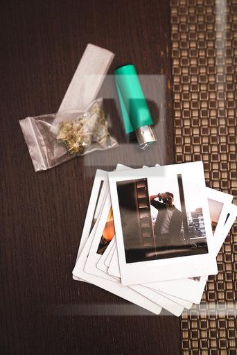 Marihuana, cigarette lighter and polaroids on wood