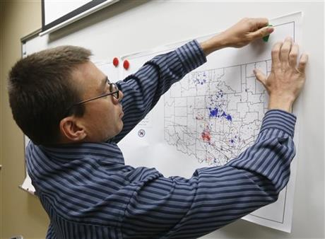 In this June 26, 2014 file photo, Austin Holland, research seismologist at the Oklahoma Geological Survey, hangs up a chart depicting earthquake activity at their offices at the University of Oklahoma in Norman, Okla.