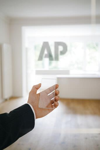Hand holding glass touch screen in refurbished home