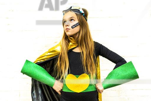 Girl in super heroine costume with band-aid on cheek