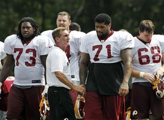 Mike Shanahan talks with offensive tackle Trent Williams