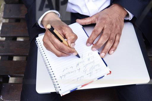 Businessman writing notes in notebook, close-up