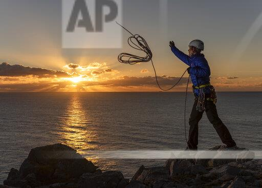 United Kingdom, Wales, Pembrokeshire, St Govan's, female climber throwing rope