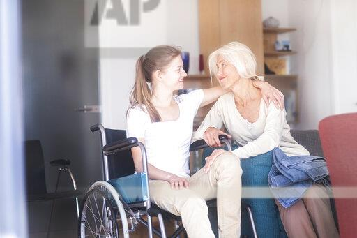 Daughter sitting in wheelchair embracing her mother