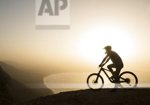 Spain, Lanzarote, mountainbiker on a trip at the coast at sunset