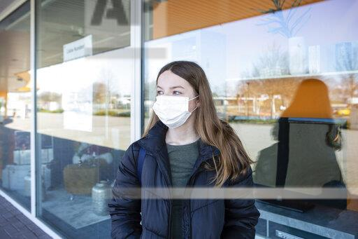 Girl with mask standing at closed shopping center