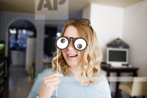 Blond woman covering eyes with funny mask