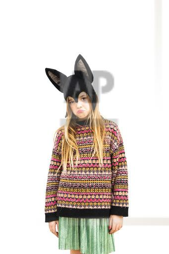 Portrait of displeased girl in bat costume in front of white wall