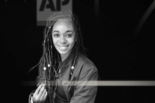 Portrait of smiling woman with dreadlocks in front of black background