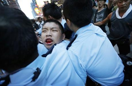 A student protester is injured after being pulled off and hit by residents and pro-Beijing supporters while local police are escorting him out of the protest area in Kowloon's crowded Mong Kok district, Friday, Oct. 3, 2014 in Hong Kong.