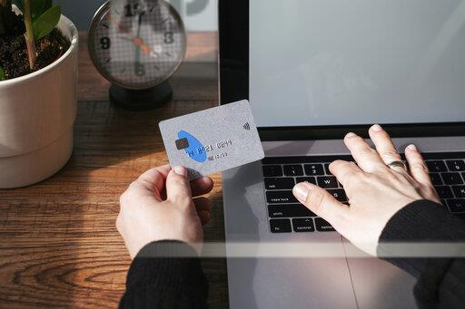 Woman using laptop and credit card for online shopping, partial view