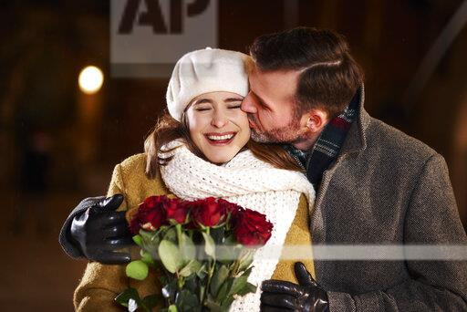 Man kissing his laughing girlfriend in winter