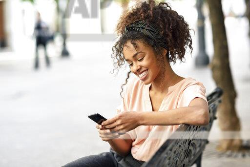 Smiling young woman sitting on a bench using cell phone