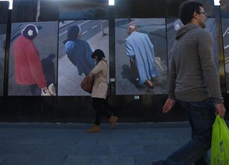 In this photo taken on Wednesday, Oct. 1, 2014, people walk past photos of shoppers on O'Connell Street, in Dublin, Ireland. The Irish Central Bank has sharply raised its economic outlook for Ireland but cautioned the government not to soften austerity plans in this month's budget, the first to be unveiled since the country's exit from an international bailout.