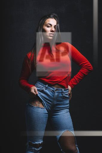 Portrait of young woman with tattoo on tigh posing in front of black background
