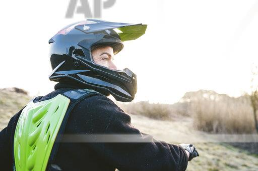 Portrait of motocross driver at sunset