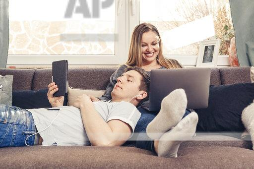 Young couple relaxing on sofa and using notebook, smartphone and ebook reader