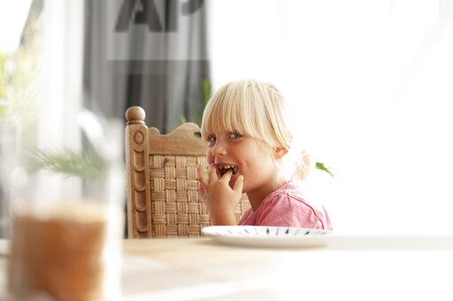 Portrait of tricksy little girl sitting at dining table eating