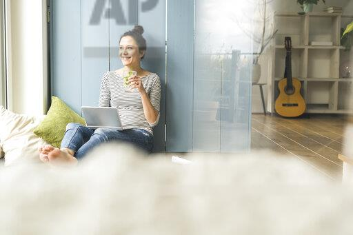 Smiling woman sitting at the window at home working with laptop and drinking infused water