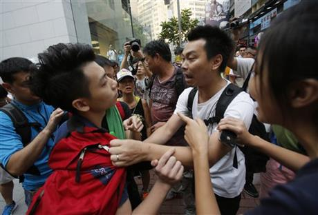 A pro-democracy student protester, left, is pressed by angry locals trying to remove the barricades blocking streets in Causeway Bay, Hong Kong, Friday, Oct. 3, 2014. Hong Kong protest leaders on Friday welcomed an offer by the territory's leader of talks to defuse the crisis over demonstrations seeking democratic reforms, though they continued to demand he resign and maintained barricades around government headquarters, frustrating staff going to work.