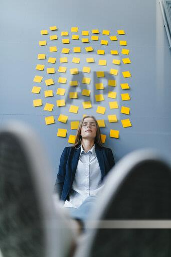 Young businesswoman sitting under data clound, relaxing with eyes closed