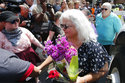 Susan Bro, center, mother of Heather Heyer who was killed during last year's Unite the Right rally, and her husband, Kim, right, speak to supporters after laying flowers at the spot her daughter was killed in Charlottesville, Va., Sunday, Aug. 12, 2018. Bro said there's still