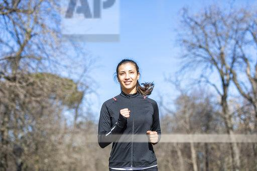 Smiling young woman jogging in park