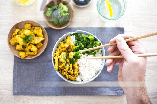 Curry chicken, broccoli and rice, man holding chopsticks with broccoli