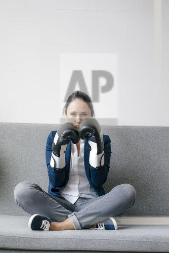Portrait of young woman sitting on couch wearing boxing gloves
