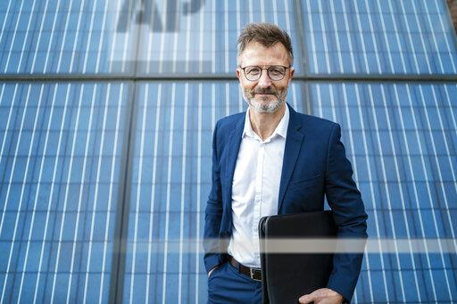 Portrait of smiling businessman holding folder standing in front of solar panels