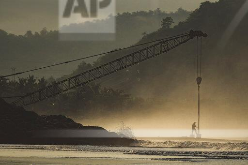 Indonesia, Sumbawa Island, Man and construction crane at seaside
