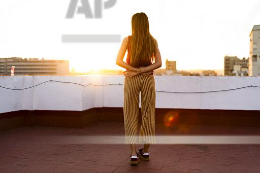 Rear view of teenage girl standing on roof terrace in the city at sunset