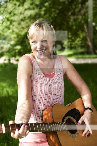 Portrait of happy senior woman playing guitar in park