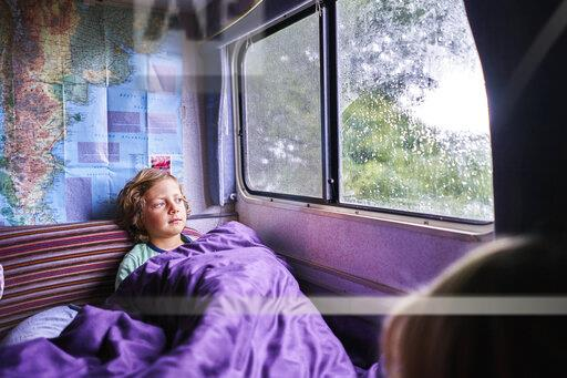 Boy in pyjama looking out of window of a camper