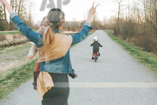 Mother carrying daughter and cheering her little son, riding bicycle