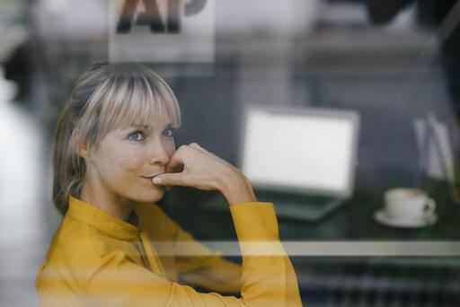 Blond businesswoman sitting at window, thinking