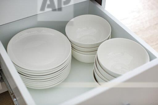 Opened drawer with white plates and bowls