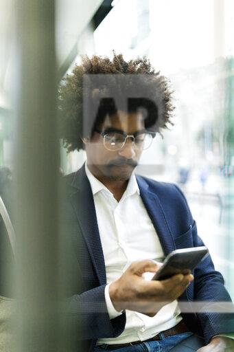 Spain, Barcelona, businessman in a tram using cell phone