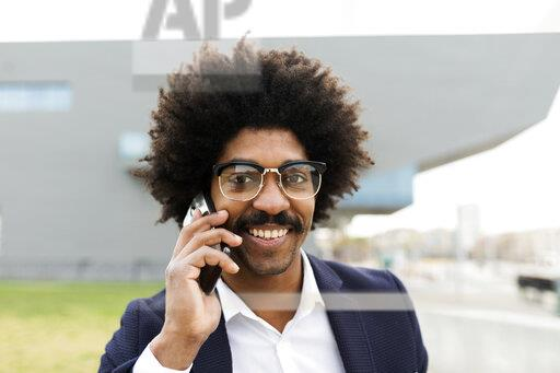 Spain, Barcelona, portrait of smiling businessman on cell phone in the city