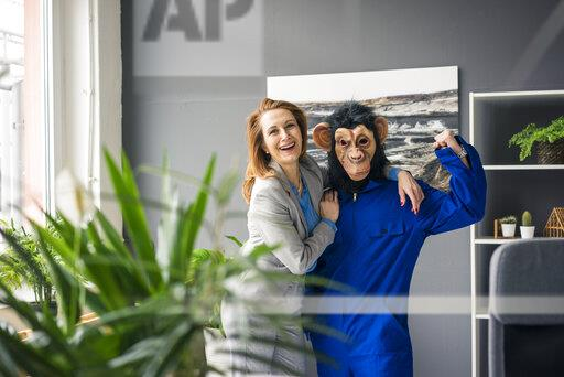 Businesswoman standing in office with a trainee, wearing monkey mask and blue oevrall