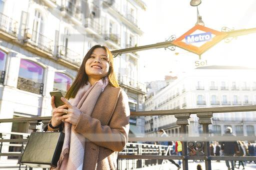 Spain, Madrid, smiling young woman at Puerta del Sol metro station with smartphone