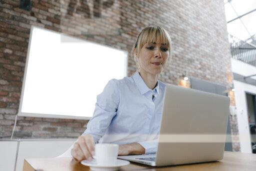 Businesswoman working on laptop, drinking coffee, licking lips