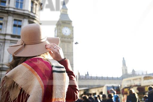 UK, London, rear view of woman wearing a floppy hat looking at Big Ben