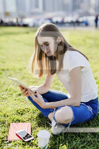 Young woman exploring New York City, taking a break, using digital tablet