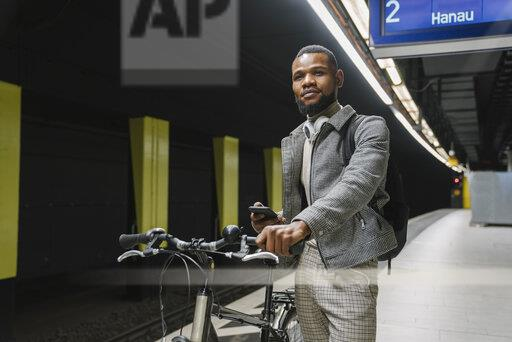Stylish man with a bicycle, headphones and smartphone in a metro station