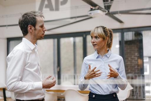 Businessman and woman standing in office, discussing