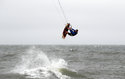 Brett Walter, from Chesapeake, Va., gets some air as he kiteboards, Thursday, Sept. 13, 2018, in Virginia Beach, Va., as Hurricane Florence moves towards the eastern shore. (AP Photo/Alex Brandon)
