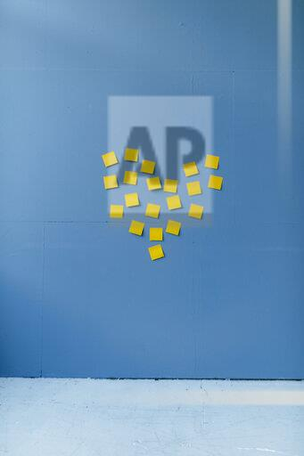 Heart-shape on a blue wall, made of yellow sticky notes