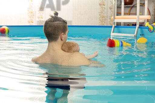 Baby swimming, father and son in swimming pool