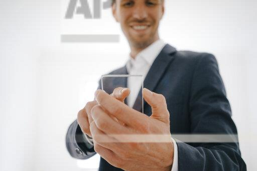 Businessman using glass touch screen in a new home